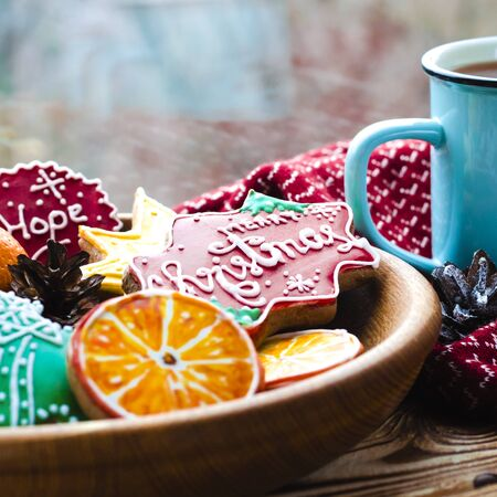 Christmas card: A cup of hot tea stands on a wooden table next to a wooden plate on which are gingerbread cookies made from orange slices against the background of a window with water drops