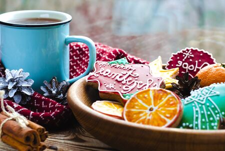 Christmas card: A cup of hot tea stands on a wooden table next to a wooden plate on which are gingerbread cookies made from orange slices against the background of a window with water drops Stockfoto