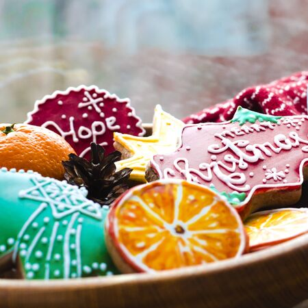 Tangerines, gingerbread cookies from orange slices, a Christmas star and greetings on Christmas lie on a wooden plate against the window