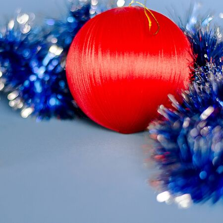 Christmas card: A red Christmas tree toy lies on a blue background. Close-up