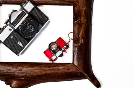 Two old camera lie in wooden frame on a white background, close-up