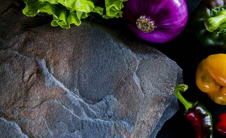 A wild multi-colored stone with a place for text lies on a black table next to fresh blue onions, yellow peppers, red chili peppers and green lettuce. Copy Space Stock fotó