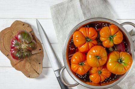 Washed various tomatoes in a colander on a wooden background with copy space top view Stock fotó