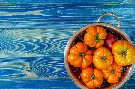 Washed various tomatoes in a colander on a wooden background with copy space top view Stockfoto - 131466985