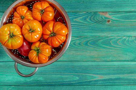 Washed various tomatoes in a colander on a wooden background with copy space top view Stockfoto - 131466986