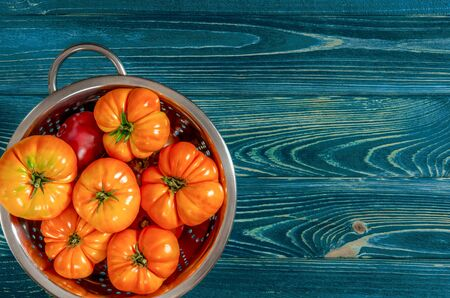 Washed various tomatoes in a colander on a wooden background with copy space top view Stockfoto