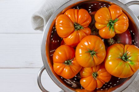 Washed various tomatoes in a colander on a wooden background with copy space top view 写真素材