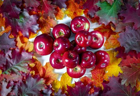 Yellow maple leaves and red juicy apples lie on a white wood background. Close-up Stockfoto - 131466996