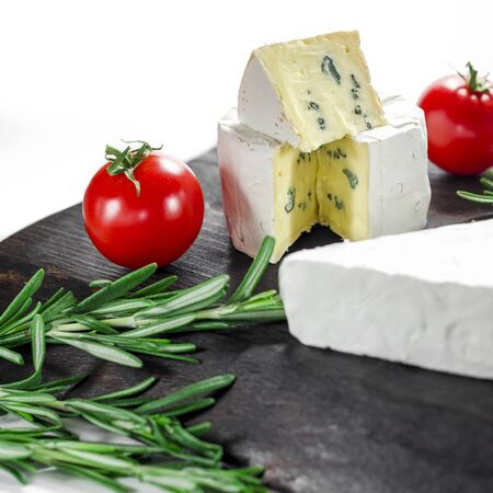 Assorted cheeses on wooden board. Camembert, cheese with blue mildew, mozzarella with tomatoes and rosemary