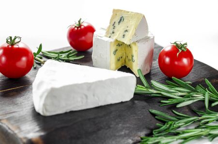 Assorted cheeses on wooden board. Camembert, cheese with blue mildew, mozzarella with tomatoes and rosemary Stockfoto - 131551614