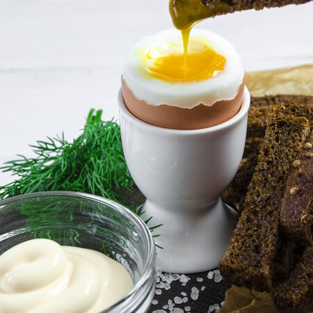 Healthy food. English breakfast with boiled egg and croutons on a white wood background. Healthy breakfast Stockfoto - 131551863