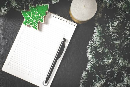 A white notebook with a black pen lies on the table next to Christmas tree decorations