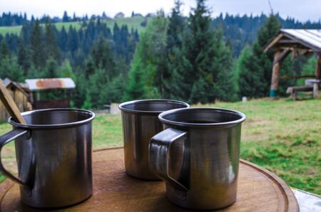 Three metal cups with morning coffee in the campaign against the background of the mountains covered with forests Stockfoto - 131551870