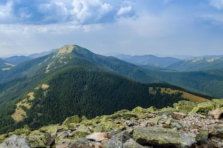 Huge stones covered with green lichen lie on the top of the mountain against the backdrop of ancient, high mountain ranges Stockfoto - 131551871