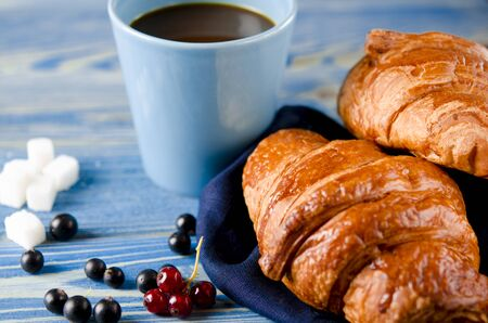 Fresh ruddy croissants with berries lie on a wooden table next to fresh black currant berries, red currants