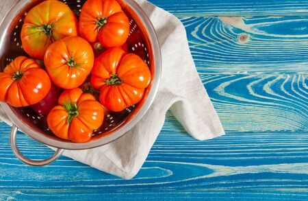 Washed various tomatoes in a colander on a wooden background Stockfoto - 131551881
