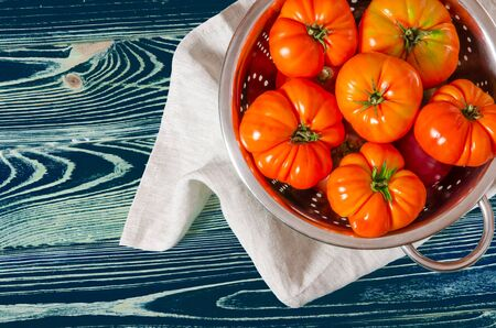 Washed various tomatoes in a colander on a wooden background Stockfoto - 131551877