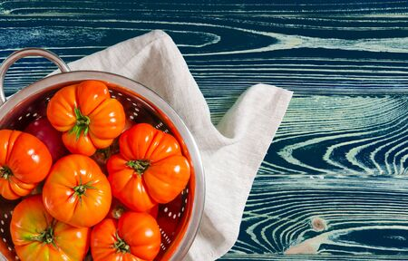 Washed various tomatoes in a colander on a wooden background Stockfoto - 131551882