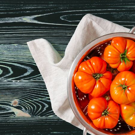 Washed various tomatoes in a colander on a wooden background