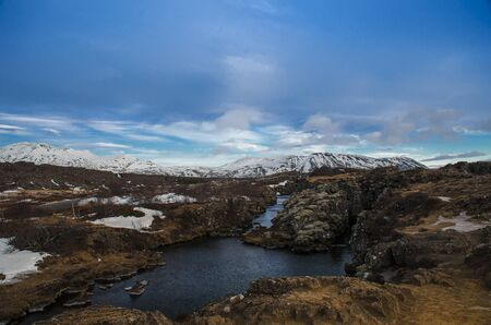 Typical Icelandic landscape: Thingvellir National Park, rivers, lava fields covered with snow against the backdrop of mountains and sky Stockfoto - 131827621