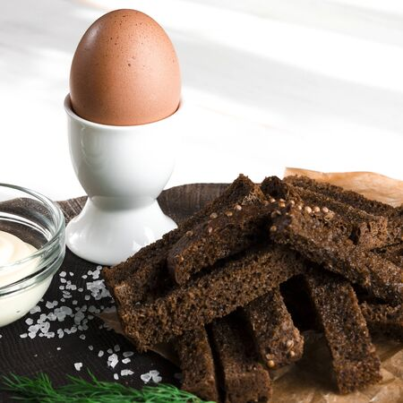 Healthy food. A boiled egg in a white ceramic stand stands on a wooden table next to rye croutons and white sauce Stockfoto - 131467250