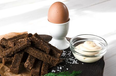 Healthy food. A boiled egg in a white ceramic stand stands on a wooden table next to rye croutons and white sauce Stockfoto - 131467248