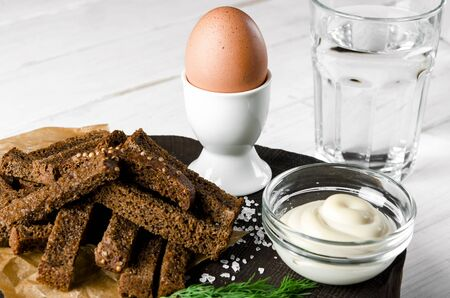 Healthy food. A boiled egg in a white ceramic stand stands on a wooden table next to rye croutons and white sauce