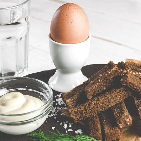 Healthy food. English breakfast. A boiled egg in a white ceramic stand stands on a wooden table next to rye croutons and white sauce Stockfoto - 131467260