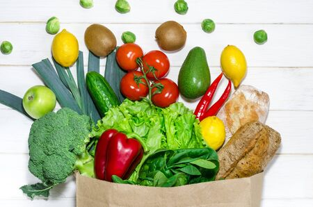 An eco-friendly paper bag with fresh food for a healthy diet. Paper bag of different health food on white wooden background. Top view