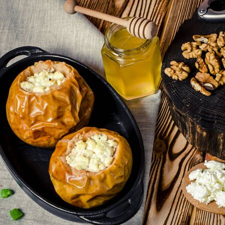 Baked apples with cottage cheese and nuts lie in a black baking dish on a wooden table next to a jar of honey and a wooden board on which nuts lie. close-up