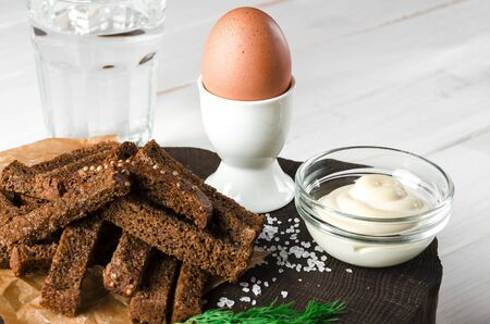 Healthy food. English breakfast. A boiled egg in a white ceramic stand stands on a wooden table next to rye croutons and white sauce Stok Fotoğraf