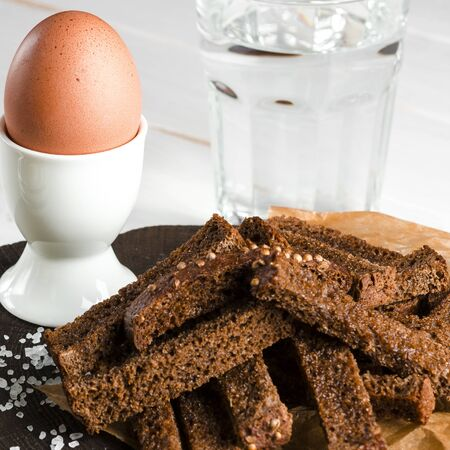 Healthy food. English breakfast. A boiled egg in a white ceramic stand stands on a wooden table next to rye croutons and white sauce Stockfoto