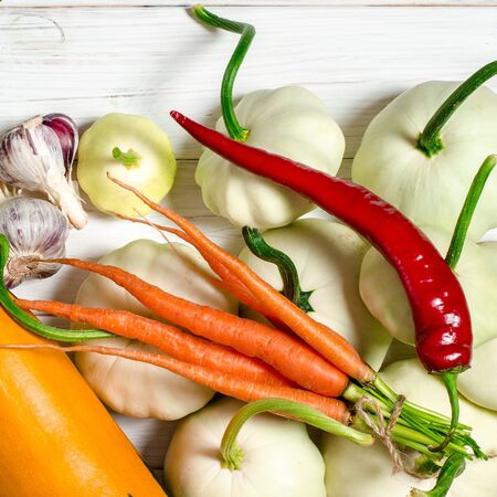 Harvest. Patisons, garlic, carrots, basil, lentils and zucchini lie on a blue woodentable. Vegetables in the on wooden table. Stockfoto