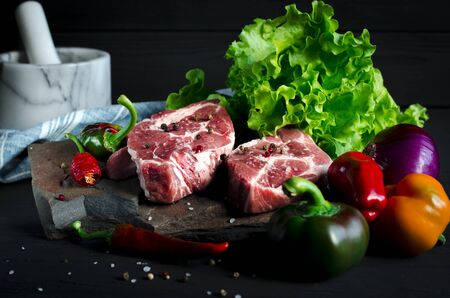 Two juicy steaks lie on a wild stone, next to red and green chili peppers and a fresh green salad on a black wooden table on which coarse sea salt is sprayed