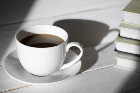 A round white cup of coffee stands on a white saucer on a white wooden table next to the shadow of the cup. Shadows and silhouettes