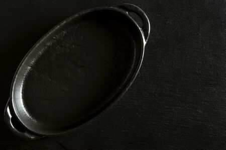 Black oval form for baking stands on a black background of stone. Close-up Banque d'images - 133066766