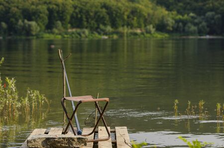 Fishermans place. A chair, a fishing rod and fish bait rests on a stone against the backdrop of a large river and green forest