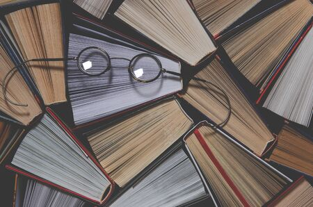 Many multicolored thick open books stand on a dark background. On the books are old round glasses. ready to read
