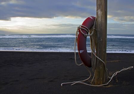 A red rescue circle to rescue people hangs on a wooden pole on the shores of the cold winter ocean. Life preserver on sandy beach