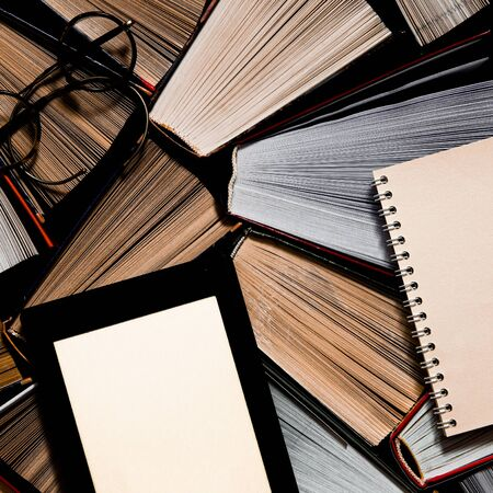 The e-book with a white screen lies on the open multi-colored books that lie on a dark background, ready to read. close-up Stock Photo