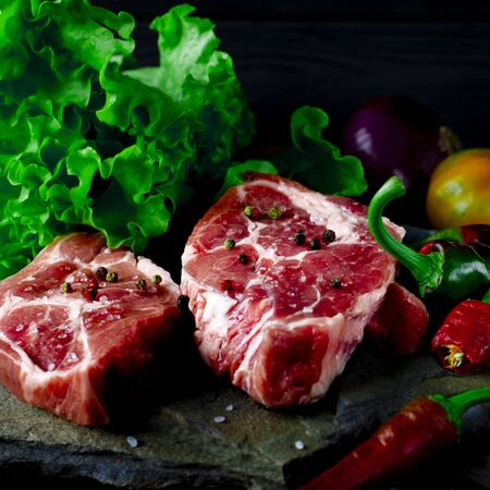 A set of raw products for the preparation of juicy meat steak with vegetables against a background of wild multicolored stone. Steak, chilli, pepper, green salad Stock fotó