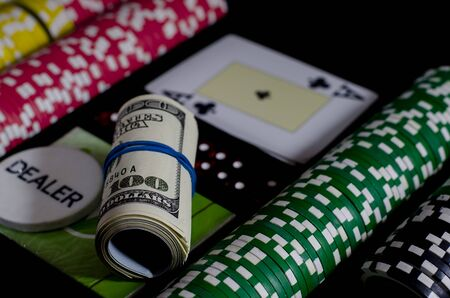 A 100 dollar kupurs is on the blackjack table next to poker chips and a dealer's chip. poker 版權商用圖片
