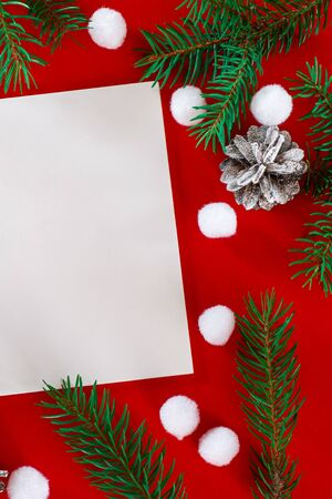 Christmas card. Frame of Christmas decoration on red background top view. Notepad with Christmas decorations on a red desktop top view