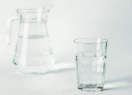Pure clear water in a glass glass and glass jug stands on a white background. isolated Stock Photo