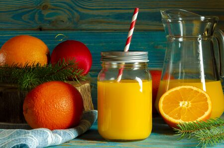 glass jar of fresh orange juice with fresh fruits on wooden table. Christmas cocktail