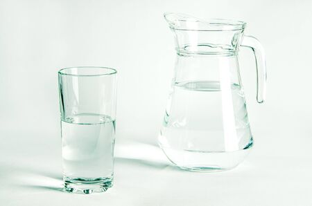 Pure clear water in a glass glass and glass jug stands on a white background. isolated