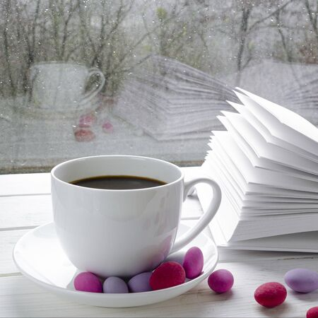 Cozy concept: a white cup of coffee stands on a white wooden table next to a white open book and colorful candy against the background of a window with raindrops and reflection on the glass