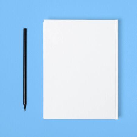 Maqueta de libro cuadrado en blanco cerrado y lápiz negro en el fondo de papel con textura de color. Maqueta de libro de tapa dura - Sobrecubierta. Fondo de pared Foto de archivo