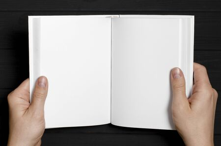 Men's hands hold a white book with clean pages. Mockup of closed blank square book