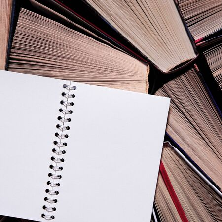 A white notebook with clean pages rests on old multicolored books ready to be read